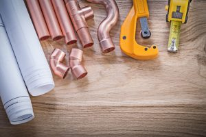 Construction plans tape line water pipe cutter fittings on wood