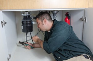 A man works on an under-the-sink garbage disposal.