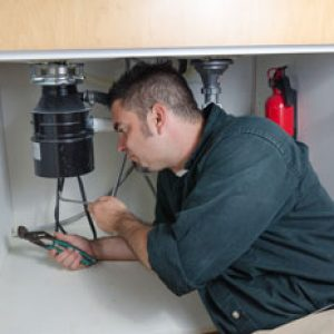 picture of plumber working on a garbage disposal